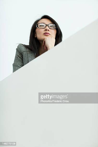 Businesswoman with hand under chin, looking away, portrait