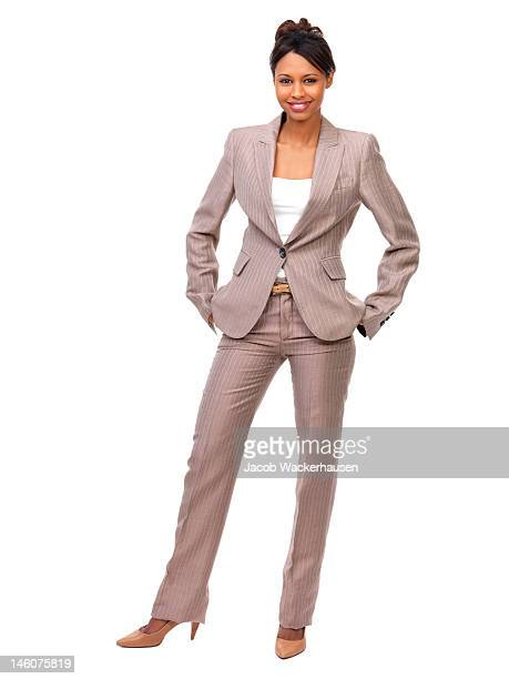 Businesswoman with hands in pockets standing against white background