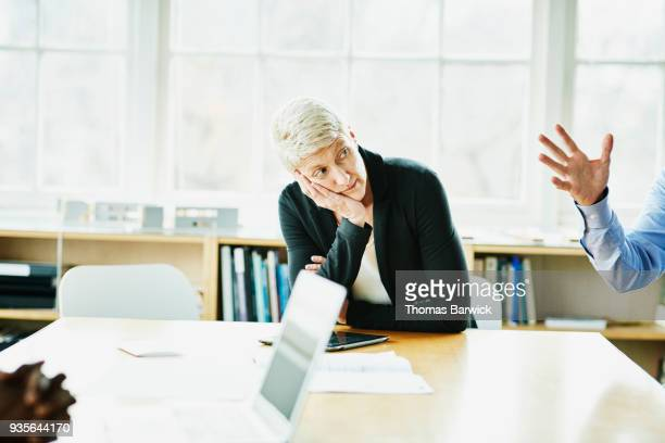 Businesswoman with head on hand listening during meeting in office conference room