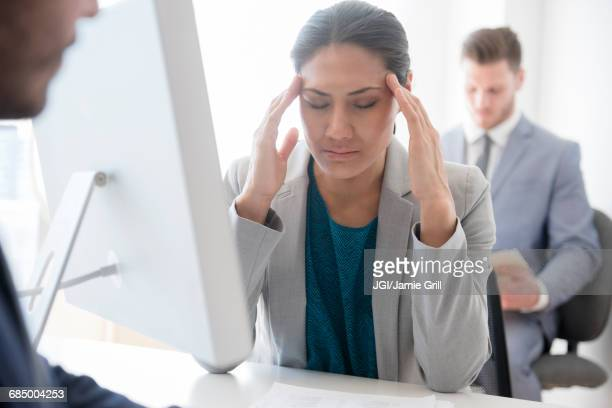 Businesswoman with headache rubbing temples in office