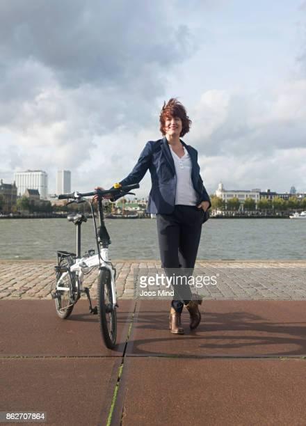 businesswoman with her folding bike, portrait