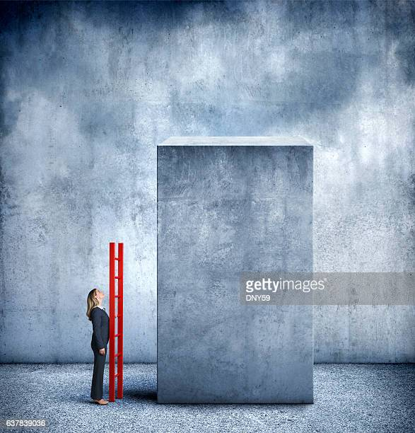 businesswoman with ladder contemplate how to reach her goal - granite stock pictures, royalty-free photos & images