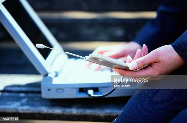 Businesswoman with Laptop and Cellular Phone