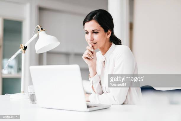 Businesswoman with laptop at table thinking