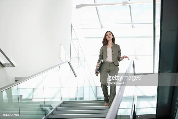 Businesswoman with laptop coming down from staircase at office