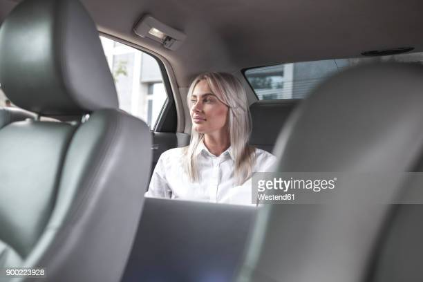 Businesswoman with laptop in car