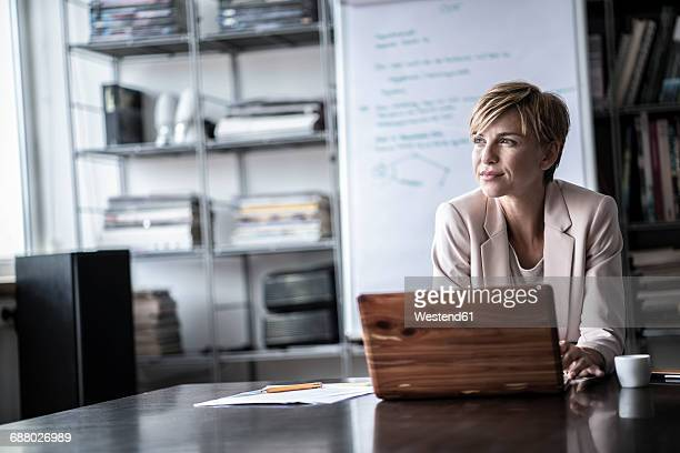 Businesswoman with laptop in modern conference room