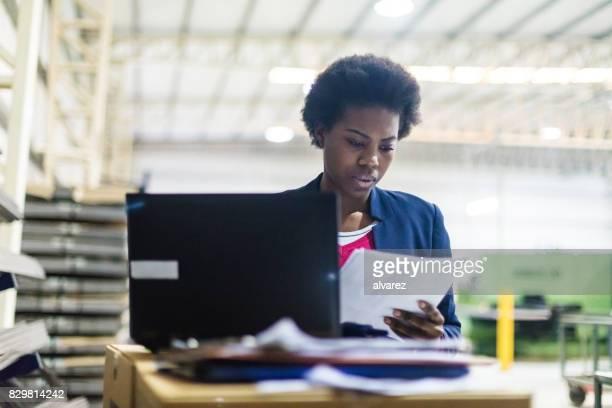Zakenvrouw met laptop lezen van een document in fabriek