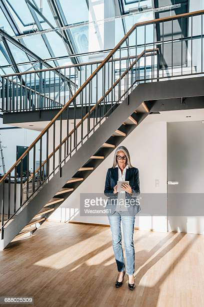 Businesswoman with long grey hair using tablet in a loft