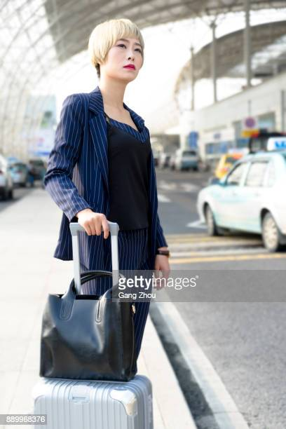 businesswoman with luggage are waiting for a cab outside airport/station