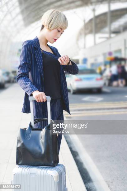 businesswoman with luggage checking the time outside airport/rail station