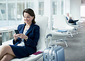 Businesswoman with luggage sitting in airport waiting area