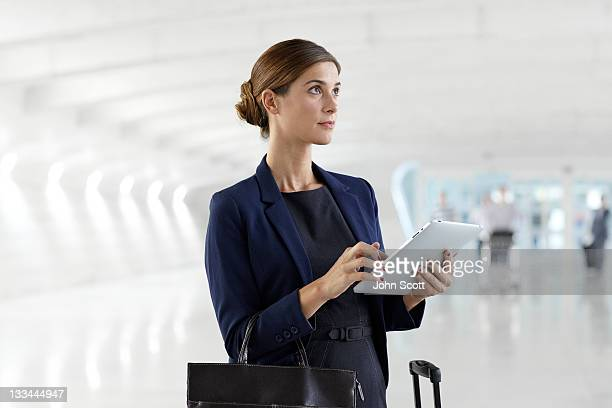 Businesswoman with luggage using tablet computer