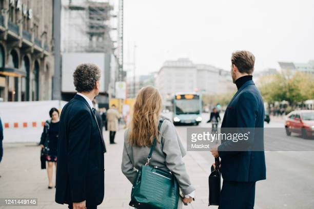 businesswoman with male coworkers standing in city - mensch im hintergrund stock-fotos und bilder