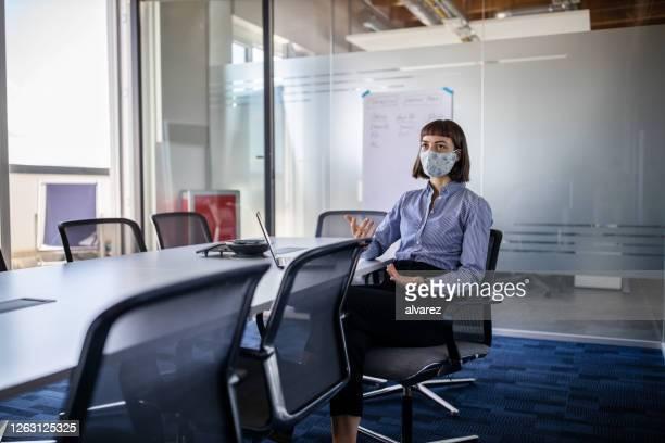 businesswoman with mask talking on a video call - aplanar a curva imagens e fotografias de stock