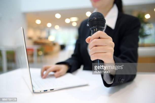 Businesswoman with microphone and laptop