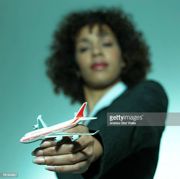 Businesswoman with model airplane