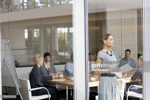 Businesswoman with paperwork looking out conference room window