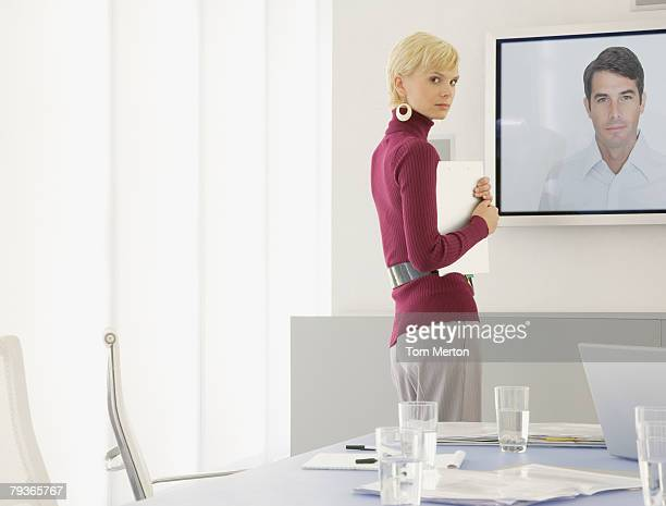 Businesswoman with paperwork standing in boardroom near a large television