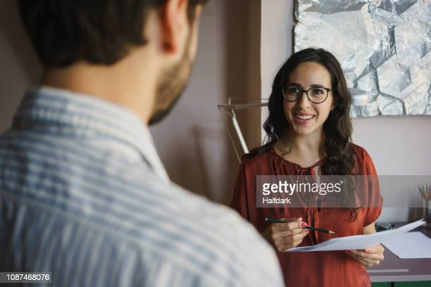 businesswoman with paperwork talking to colleague in office - 肩越し ストックフォトと画像