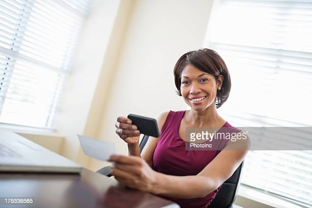 Businesswoman With Phone Depositing check