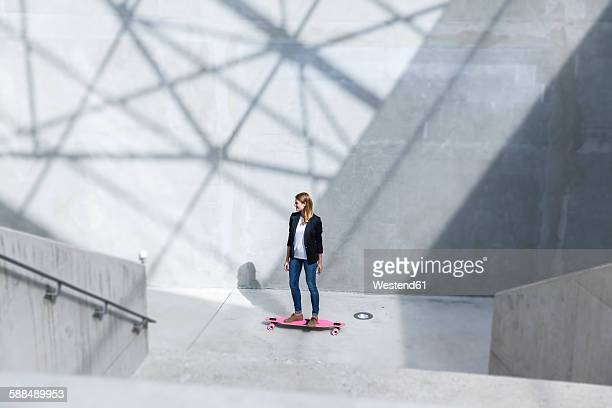 Businesswoman with pink skateboard in modern architecture
