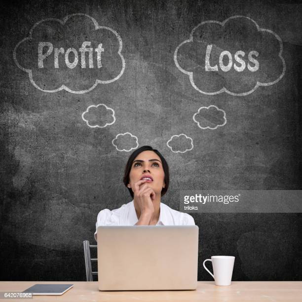 Businesswoman with profit and loss thought bubble