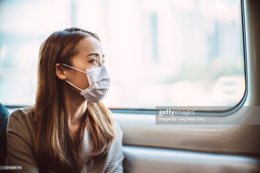 Businesswoman with protective face mask looking out of the window of train in thought : Stockfoto