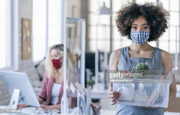 businesswoman with protective face mask quits job due to limiting workplaces in office, during covid-19 - quitting a job stock pictures, royalty-free photos & images