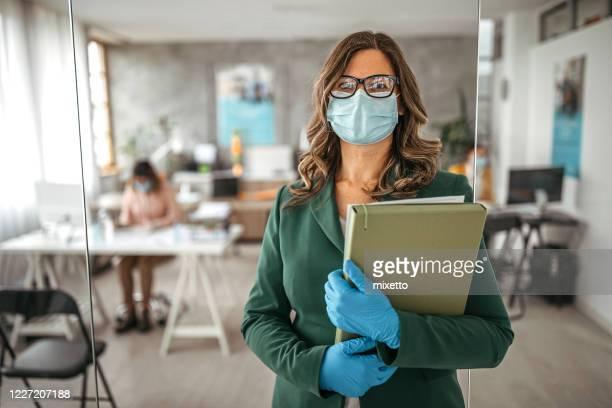 mujer empresaria con guantes de protección y mascarilla facial en la oficina - devolución del saque fotografías e imágenes de stock