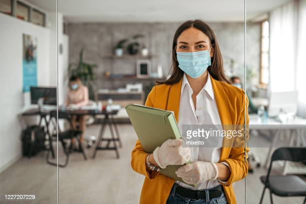 businesswoman with protective gloves and face mask at office - avoidance stock pictures, royalty-free photos & images