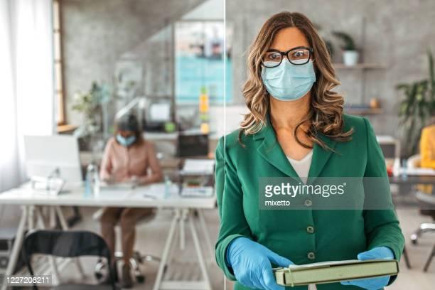 imprenditrice con guanti protettivi e maschera facciale in ufficio - rinviare la palla foto e immagini stock