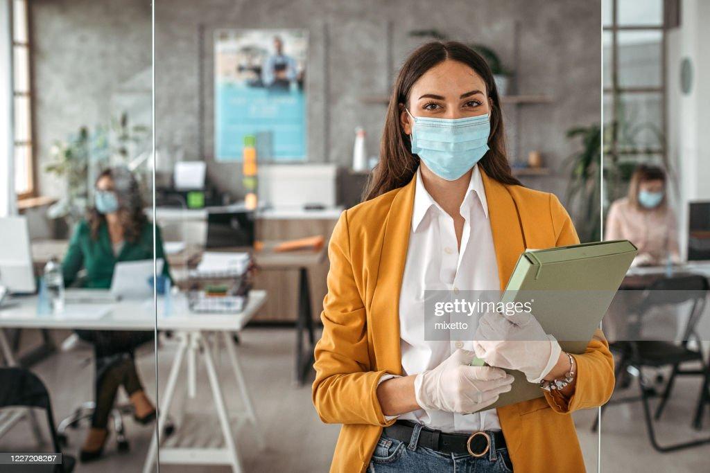 Imprenditrice con guanti protettivi e maschera facciale in ufficio : Foto stock
