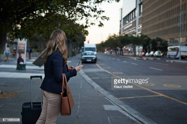 Businesswoman with shoulder bag hailing a cab with her phone