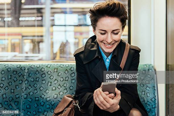 Businesswoman With Smart Phone In Commuter Train
