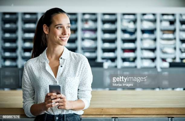 businesswoman with smart phone in textile factory - da cintura para cima imagens e fotografias de stock