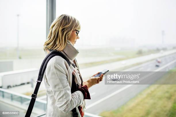 Businesswoman with smart phone standing at the airport