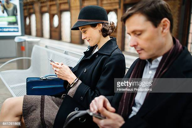 Businesswoman with Smart phone waiting for Train