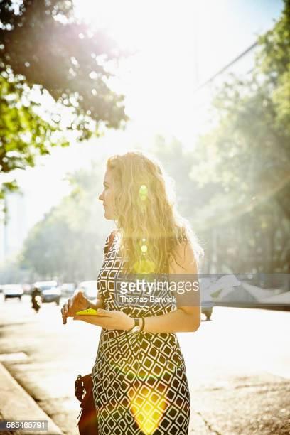 Businesswoman with smartphone on city sidewalk