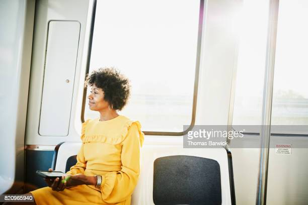 Businesswoman with smartphone sitting on commuter train looking out window