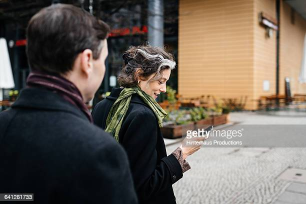 businesswoman with smartphone walking on street - following stock pictures, royalty-free photos & images