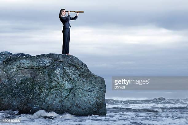 Geschäftsfrau mit Spyglass Blick auf raues Meer