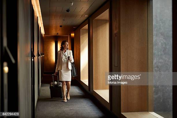 Businesswoman with suitcase at hotel corridor