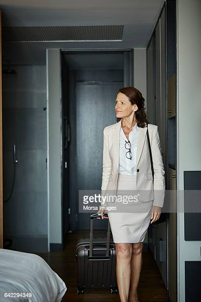 Businesswoman with suitcase entering in hotel room