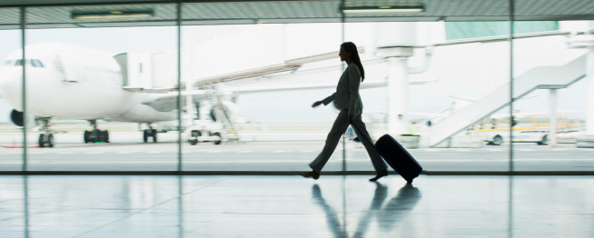 Businesswoman with suitcase in airport - gettyimageskorea