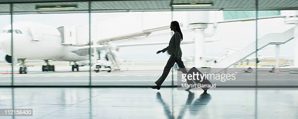 businesswoman with suitcase in airport - beat the clock stock photos and pictures
