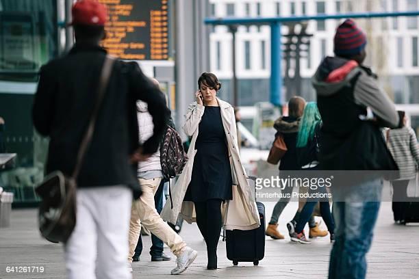 businesswoman with suitcase using smartphone - pendler stock-fotos und bilder