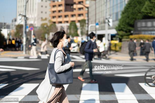 市内を歩く外科マスクを持つビジネスウーマン - 感染症 ストックフォトと画像