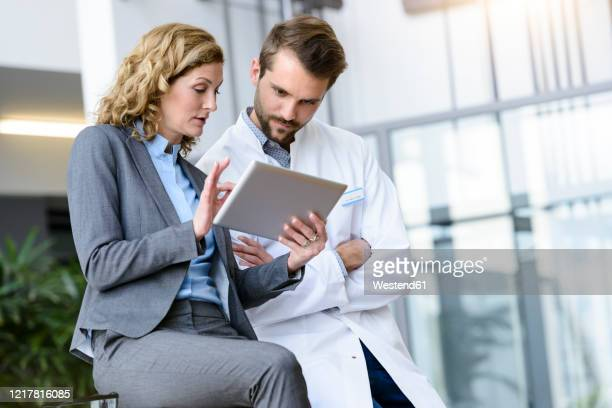 businesswoman with tablet and doctor talking in hospital - 営業職 ストックフォトと画像