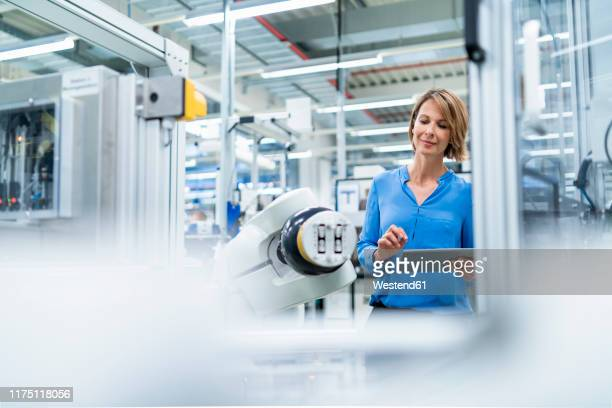 businesswoman with tablet at assembly robot in a factory - blue blouse stock pictures, royalty-free photos & images